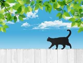 新鲜的绿色与黑猫和白色的木栅栏
