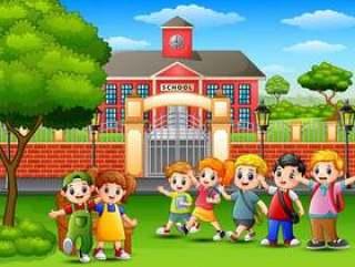 站立在教学楼前面的愉快的小学生